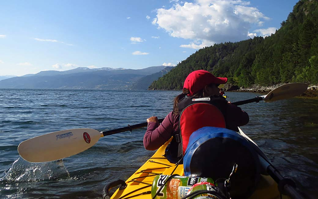 Woman in a kayak, viewed from behind with coastline featuring mountains in the distance
