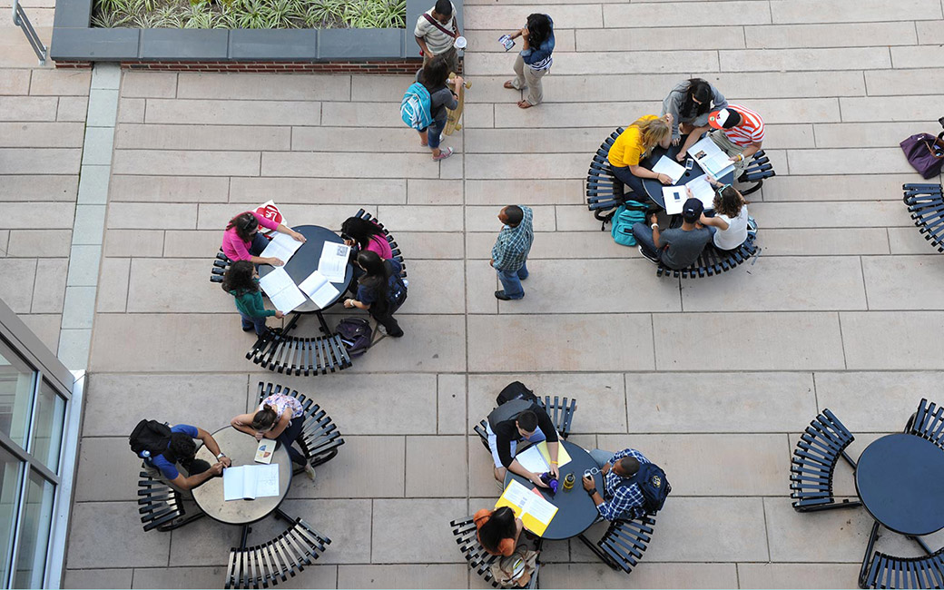 Air view of students sitting at picnic tables on campus