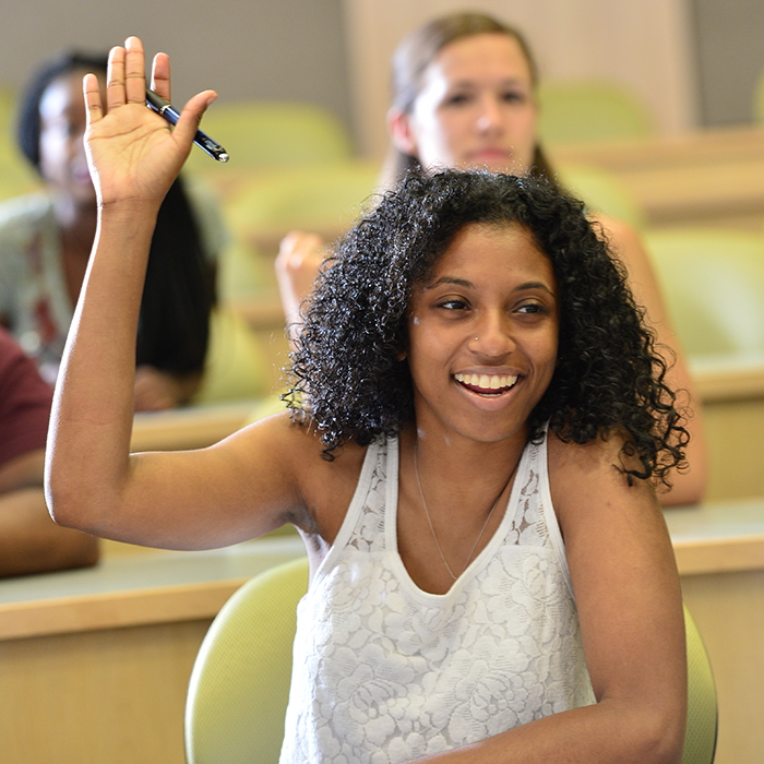 Smiling student raising her hand in classroom