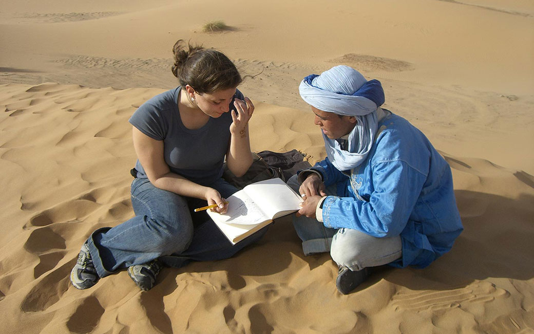 two people in sand studying