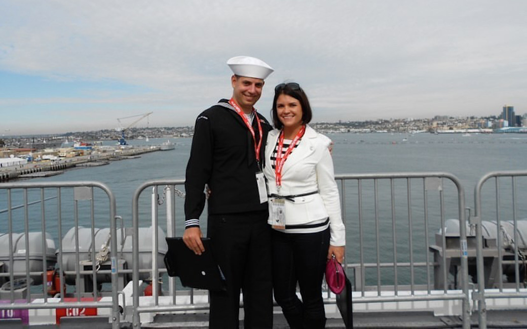Color image of a white male sailor and a white woman outdoors