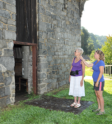 Two women next to a stone building