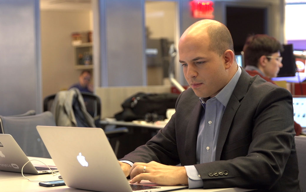 "Towson University alumnus Brian Stelter '07 works on a story inside the CNN newsroom. Stelter hosts the CNN show ""Reliable Sources,"" which won the Walter Cronkite Award for Excellence in Television Political Journalism."