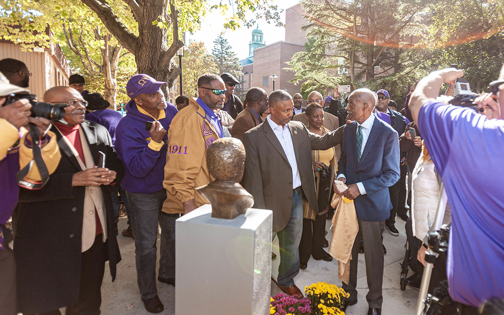"Julius ""Dean"" Chapman, far right, unveils a bronze bust in his honor outside TU's Media Center on Oct. 19, 2019."