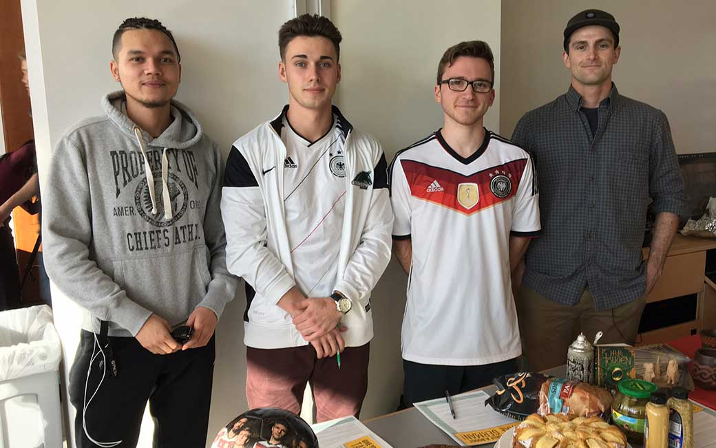 (l-r) Marco Preiner, '18, Regis Breen, '18, Alexander Jantsch, '17,  and Matt Conner, '17, prepared their German table for the Foreign Languages Day, including German potato salad, candies, pastries, beer steins and a soccer ball.