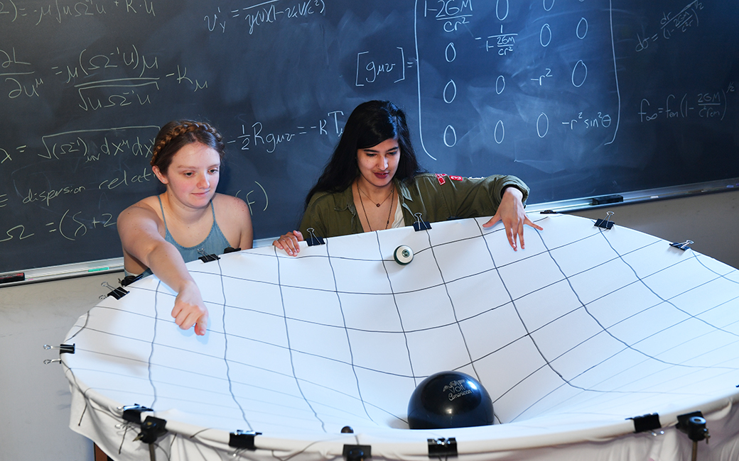Rachael Huxford (left) and Hamna Ali interact with a model of a black hole built by professor James Overduin.