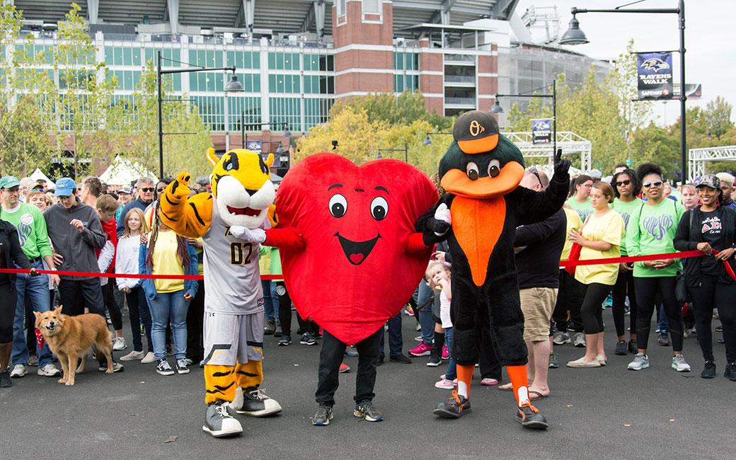 Doc, heart mascot and Oriole bird mascot at start line of heart walk