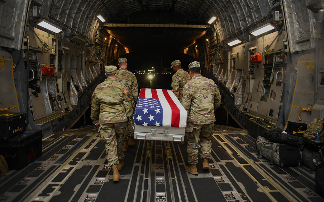 Soldiers carrying flag draped casket out of plane