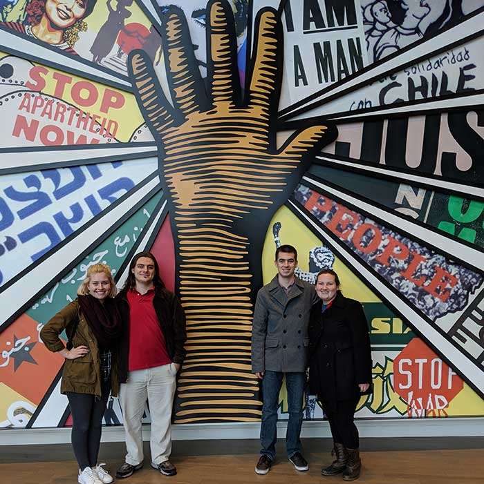Four students standing in front of a mural