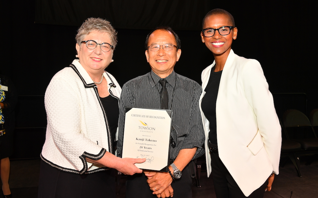 Kanji Takeno pulled triple duty as a service award honoree, a USM Board of Regents staff awards finalist and event photographer at the 48th-annual TU Service Awards Celebration. He is flanked by President Kim Schatzel (left) and Vice President, Marketing Communications Marina Cooper.