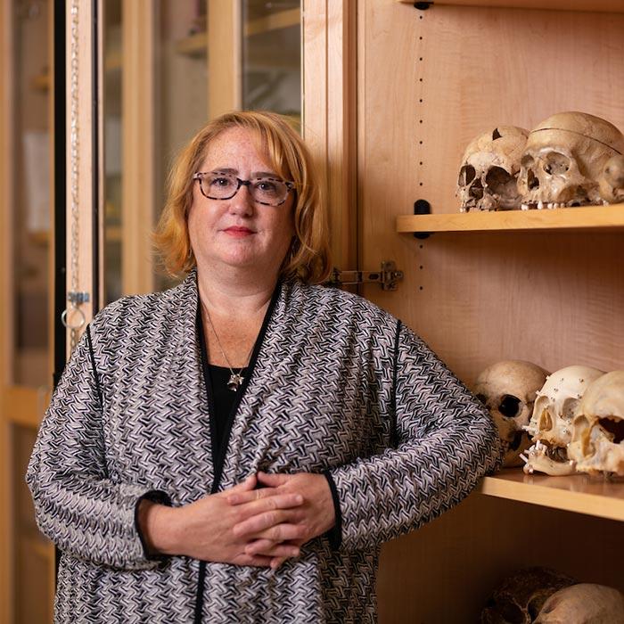 Dana Kollmann portrait next to shelf with skulls