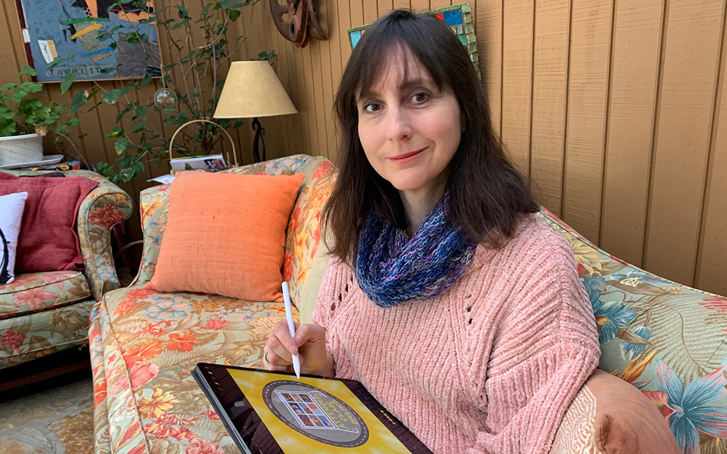 Professor Lynn Tomlinson sits on her couch with an iPad and stylus in her hand