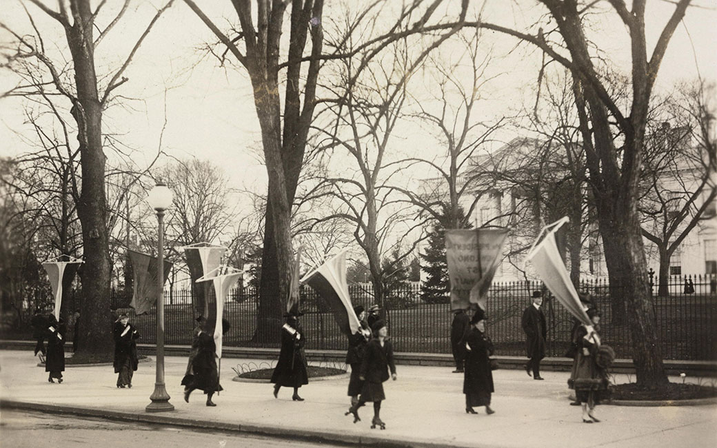 Black and white photo of suffragists with banners and flags on sidewalk outside of White House