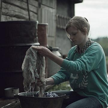 Film still of woman washing in bucket