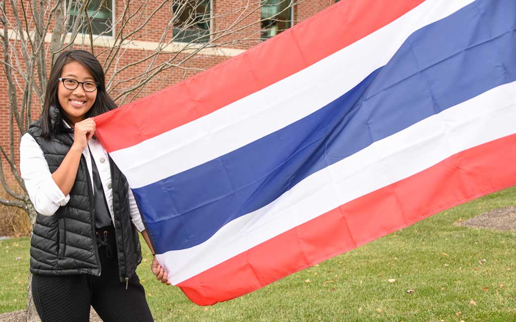 "Supitha ""Mook"" Phawapoothanon '20, standing with the Thai national flag on the International Walkway."