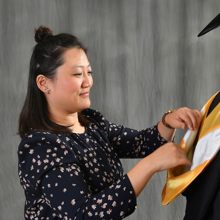 Pei Ge practicing robing a graduate
