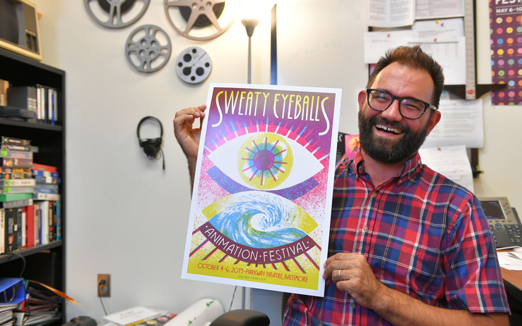Professor Phil Davis holds up a poster for the Sweaty Eyeballs Animation Festival