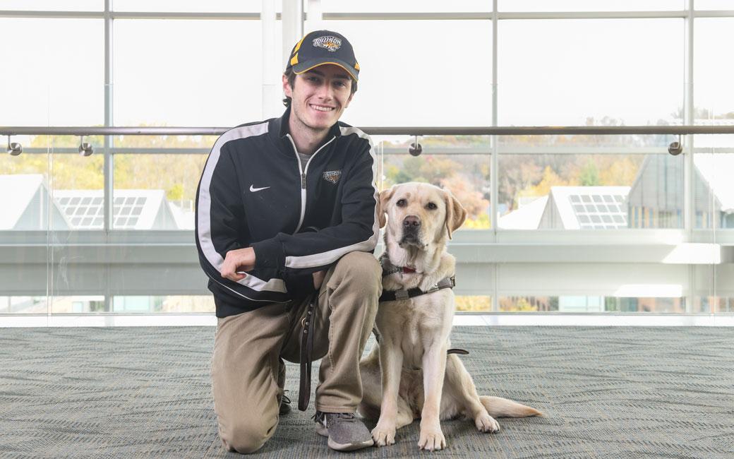 Tim Utzig '20 with his service dog Alisa