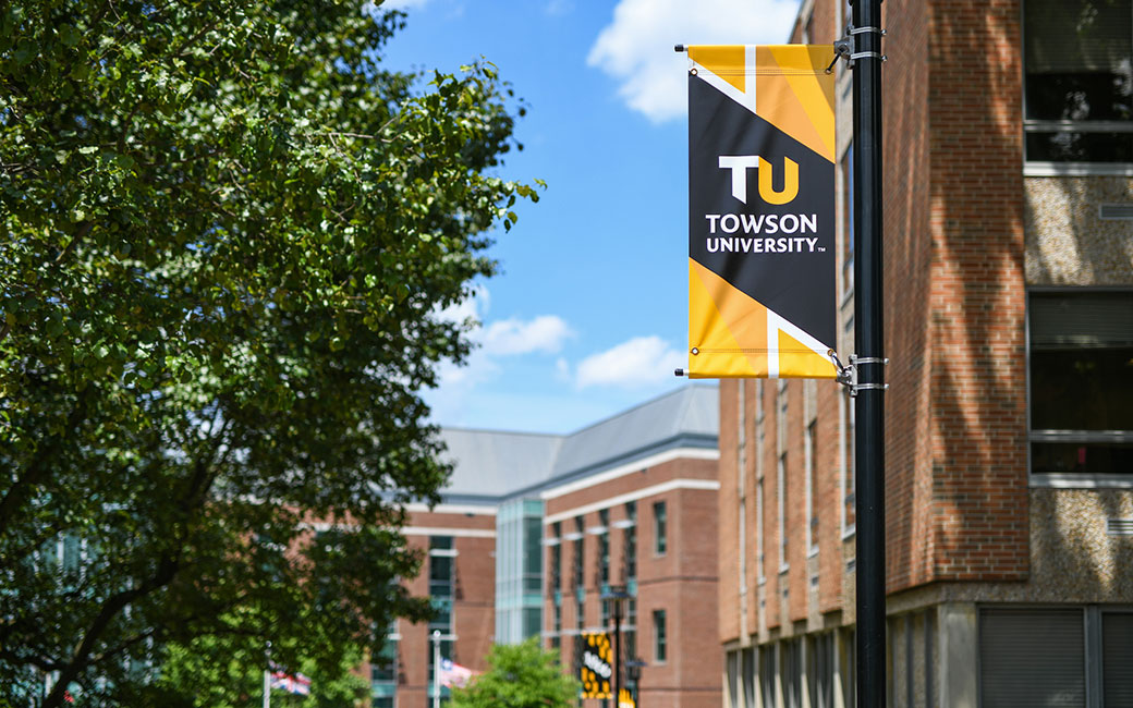 TU branded banner on lamp post with tree foliage and Liberal Arts building in background