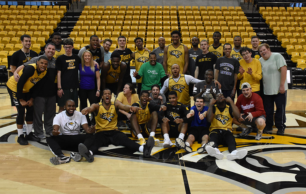 Members of the Towson University men's basketball team pose with members from the Hussman Center for Adults with Autism during a special clinic held at SECU Arena.
