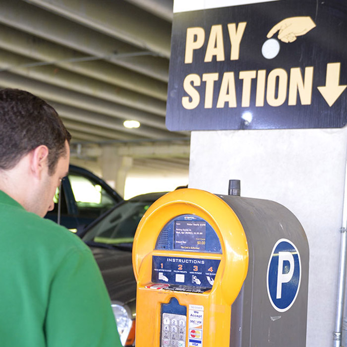 Student using a parking lot pay station.