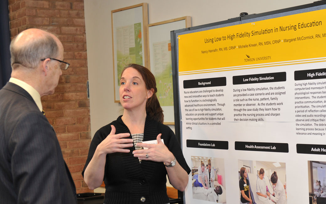 faculty presenting a poster