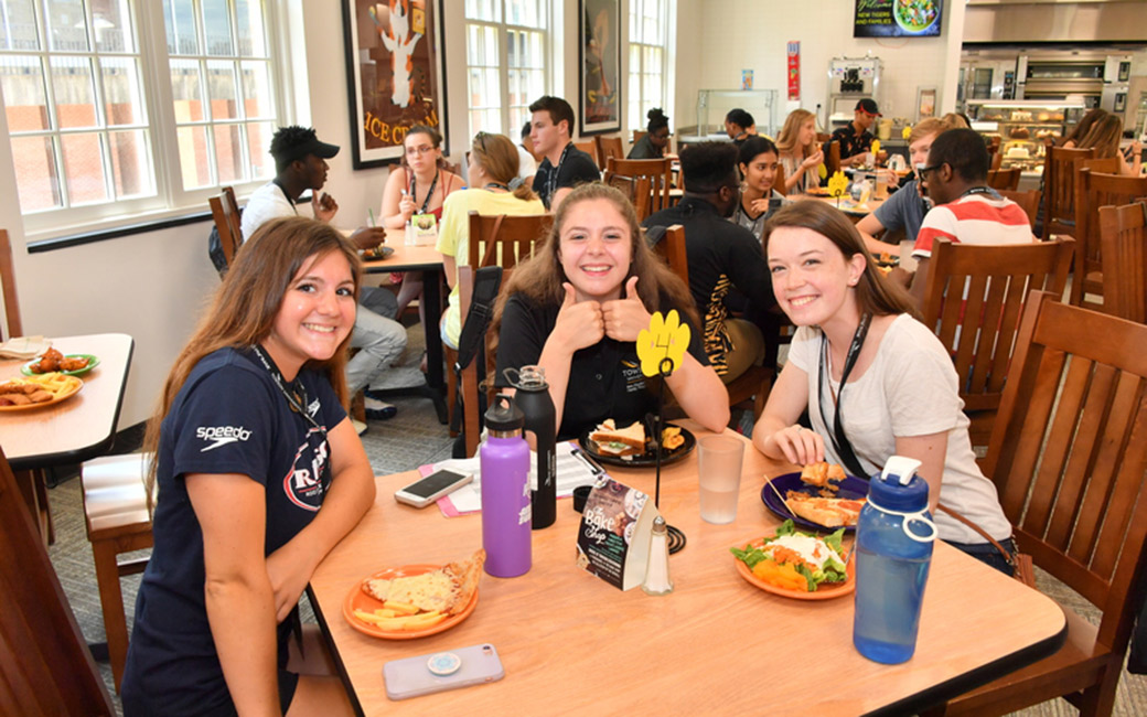 Orientation leader and two students smiling at lunch