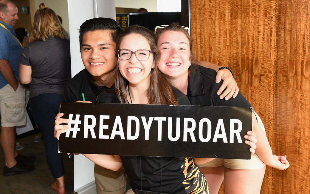 students smiling holding Ready TU Roar sign