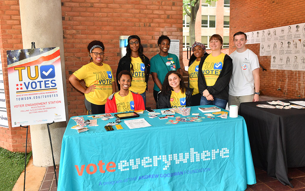 group of student volunteers at a voter engagement table under the Lecture Hall