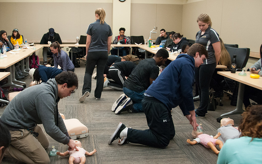 TU student providing CPR instruction