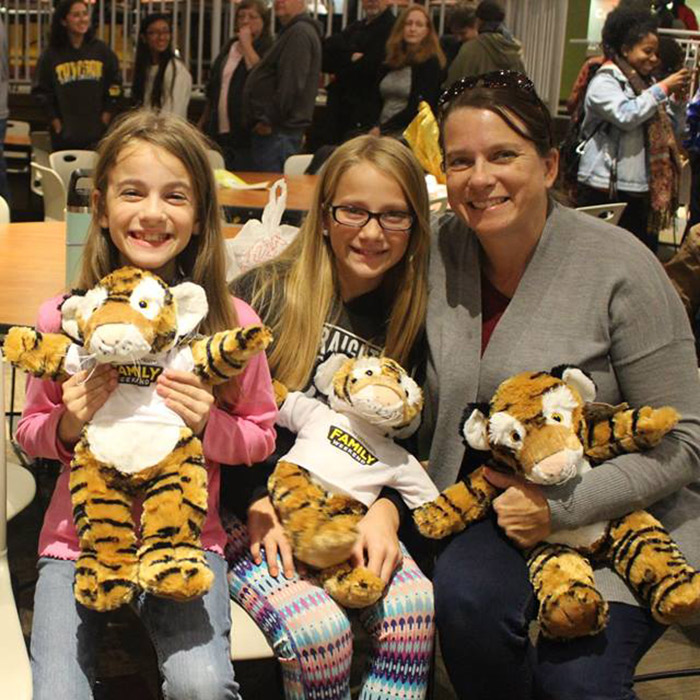 family smiling with stuffed tigers