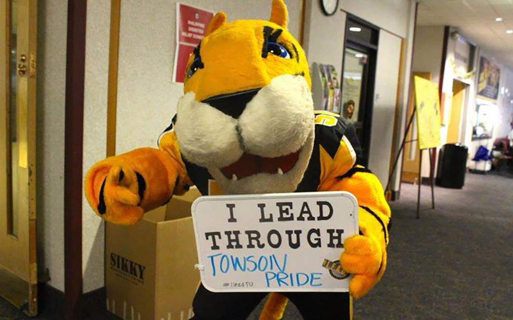 "Doc holding a sign that reads ""I lead through Towson Pride"""