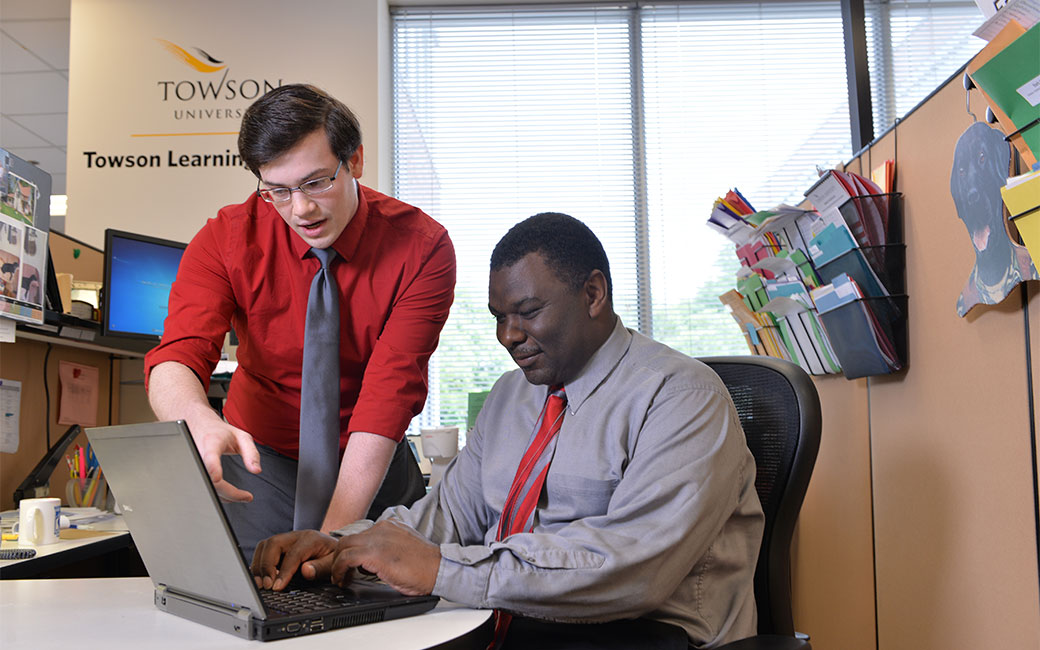 Staff member helping client with laptop at desk