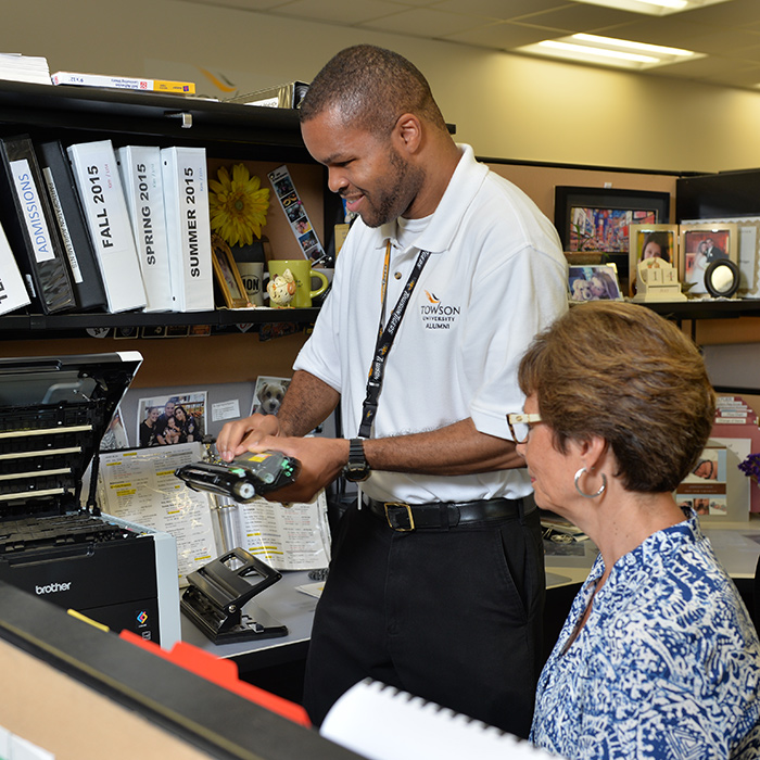 man helping woman at a printer