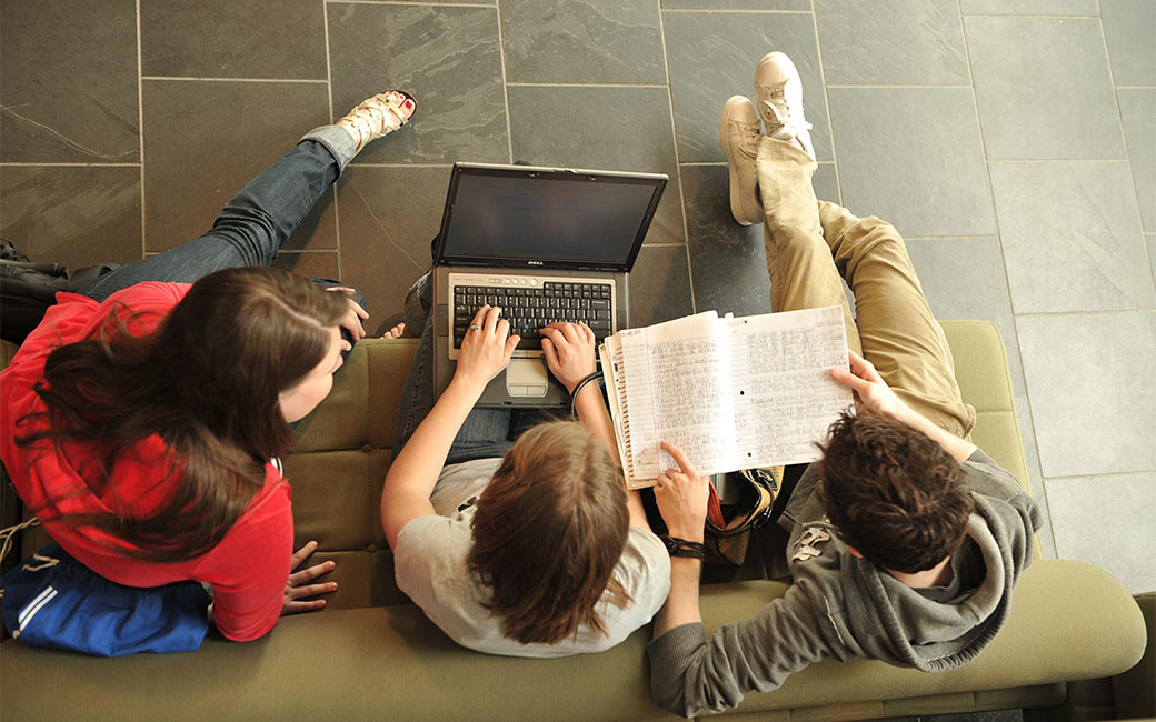 Students working together on a laptop in a lounge