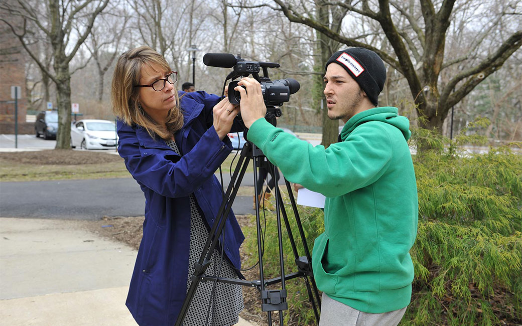 professor and student adjusting digital video camera