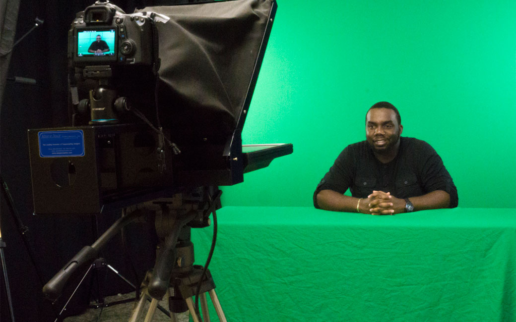 A student in SCS studio C is seated in front of a teleprompter with a green screen behind