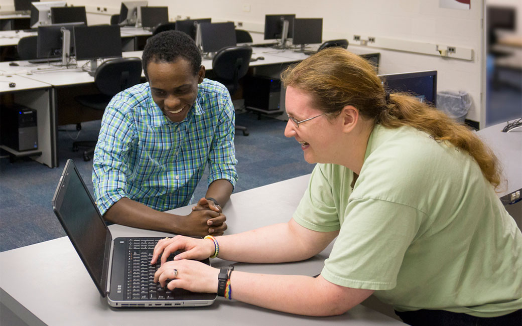 SCS staff help a student troubleshoot a laptop problem