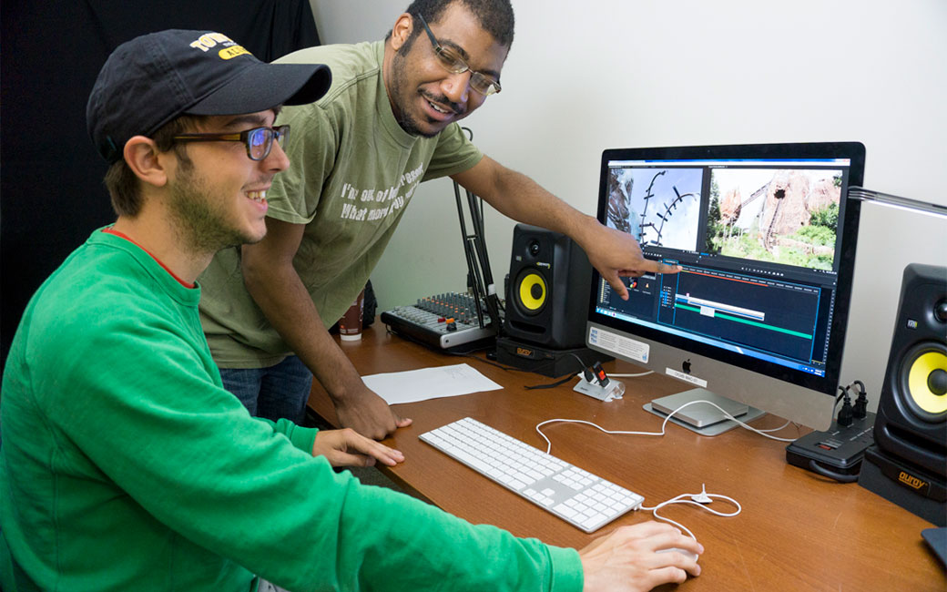 SCS staff assisting a student with video editing