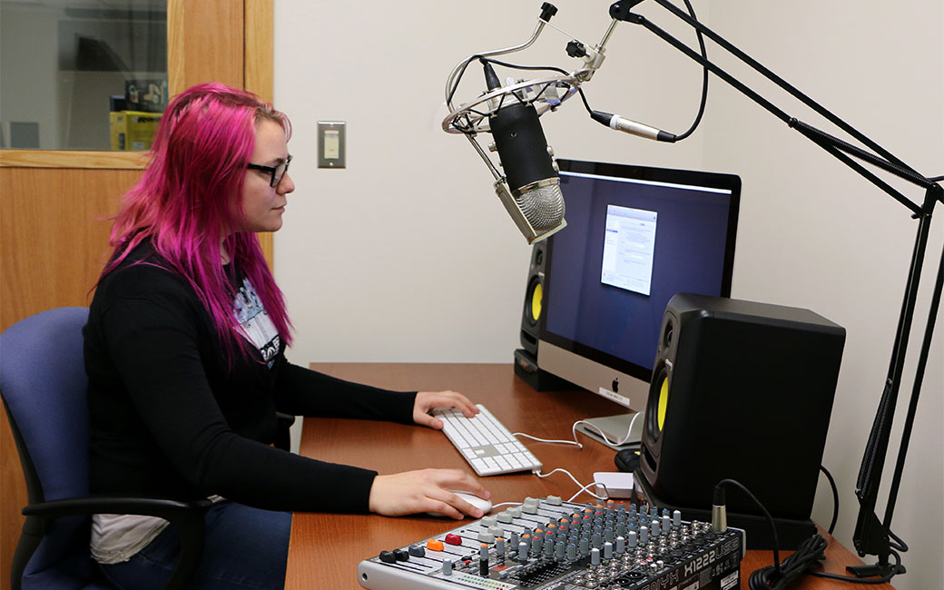 Female student works on a voiceover project in Studio A