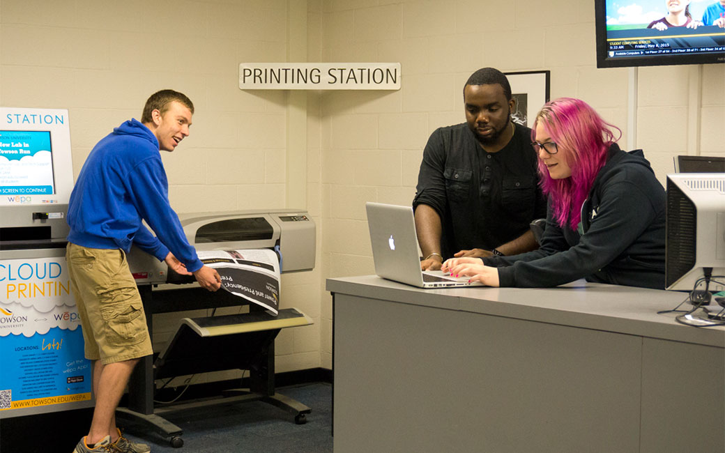 a student prints a poster while staff help with a laptop problem nearby