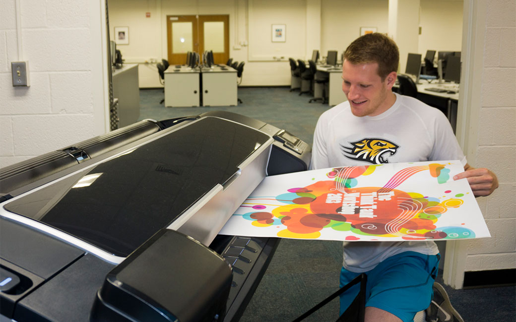 Male student on knee pulling poster off of large-format printer